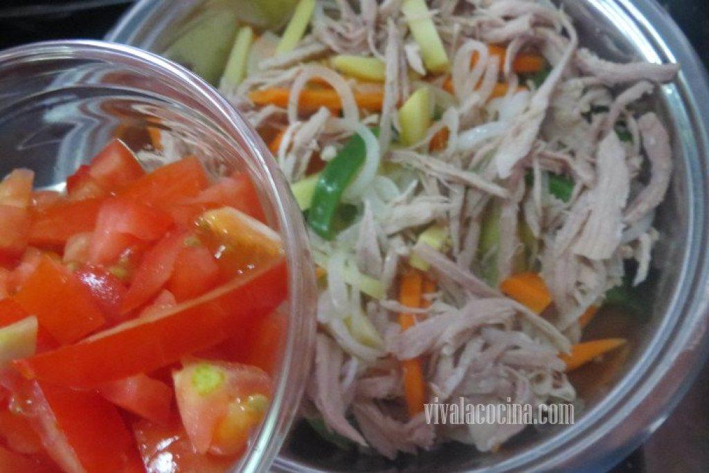 Añadir el Tomate y mezclar los ingredientes para la Pierna de Cerdo con Chile Guajillo