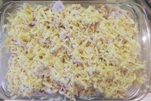 Bandeja con la pasta con champiñones, jamón y queso antes de meter al horno