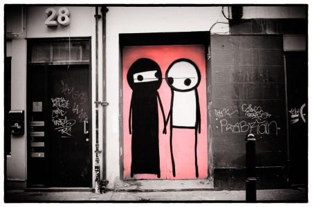 Street art in East London, two figures on a door, by artist Stik