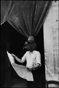 A man reading a newspaper, his head is superimposed by a curtain knot in the foreground
