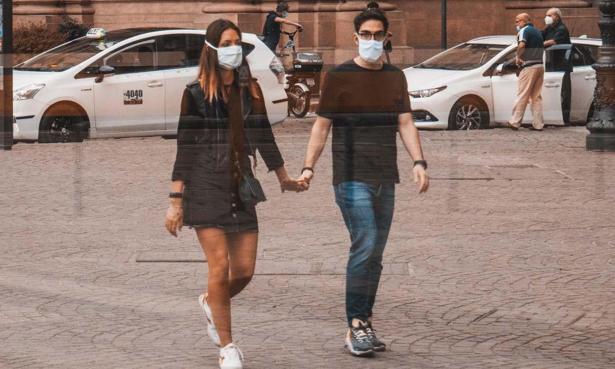 pareja con cubrebocas camina por las calles de Roma
