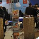 CHRISTIAN TOUR - Stand expozitional personalizat cu structura din grinda de aluminiu cu zabrele, pupitru info, scaune de bar, podium iluminat in cant, grafica de stand personalizata.