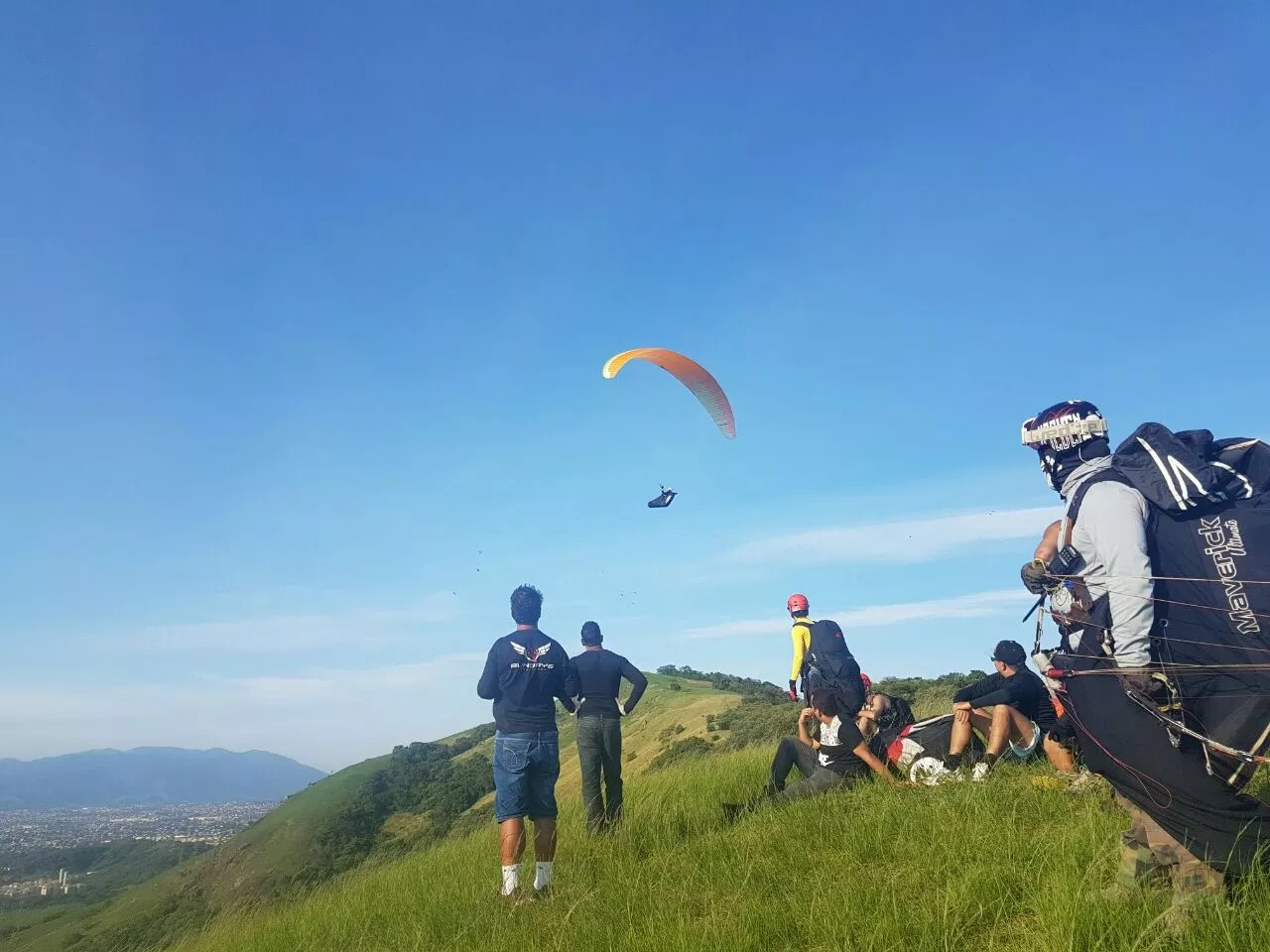 A group of people flying kites on a grassy hill - Paragliding