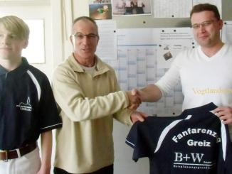 Andreas Beierlein (rechts) übergibt Michael Lippert die neuen Poloshirts