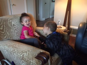 Vienna and Ryker very animated as she sits on an upholstered chair and he reaches over to tickle her