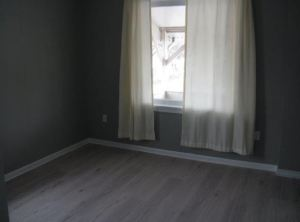 room redone with soft grey, white curtains and a wood floor
