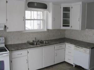 Pristine white cupboards and a granite-look counter top erase all memories of the previous kitchen's mess