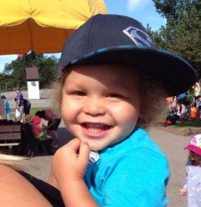LIttle boy in a light blue shirt and dark blue baseball cap smiling brightly