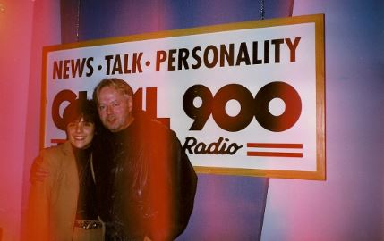 Michael Burgess and I, arm in arm, in front of the News-Talk-Personality-CHML-900 banner in that radio station's control room