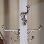 cream-coloured coat rack with small, soft-grey owl on top. Silver coat hooks on all four sides.