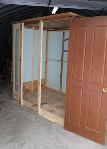 framed walls are up, a door is ready to be installed and a tall, thin window can be seen on the far left