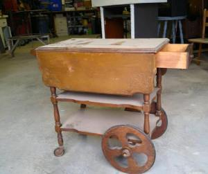 antique tea trolley with castors on the front legs and large wheels on the back