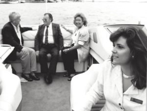 Riding on a boat in Lake Ontario. Doug at far left talking to some older, obviously wealthy couple, and me smiling in the foreground