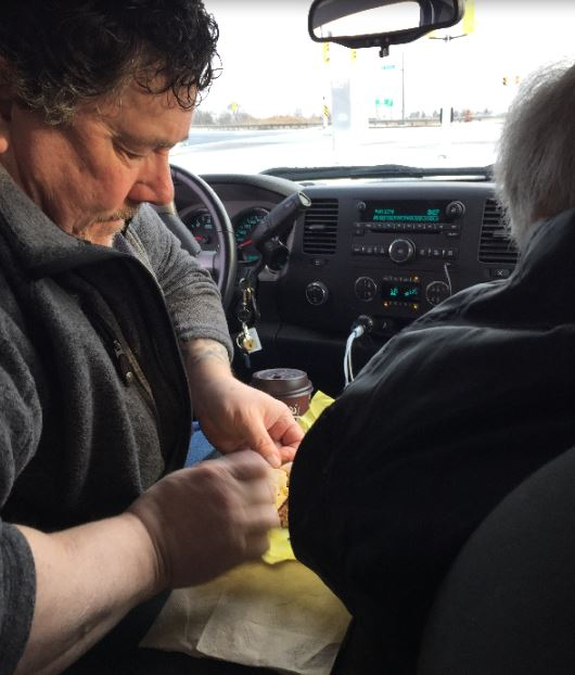 Taken from the back seat of the truck, Derek is separating the sections of Dad's egg McMuffin, while Dad waits
