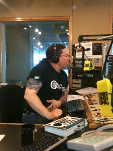 Derek talking into a microphone, on air at Bob FM in London