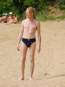 skinny white man with a ponytail and navy bathing suit standing on the sand, looking into the distance