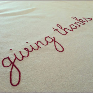 giving thanks written in lower case red script across a canvas