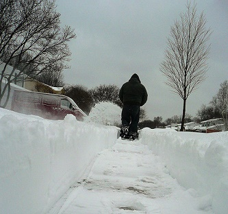 Shot of a cleared sideway as a person with a snowblower works up ahead