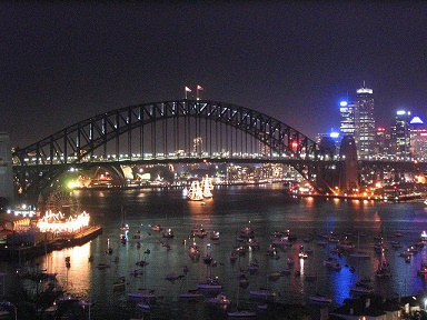 nighttime view of Sydney Harbour with hundreds of boats in the foreground and purple and gold lights on a bridge and along the shorelines