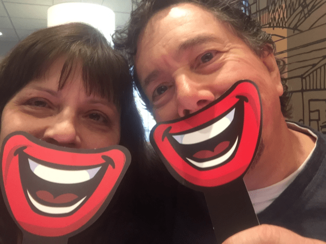 Derek and I holding cardboard cartoon smiles up to our mouths in a McDonald's