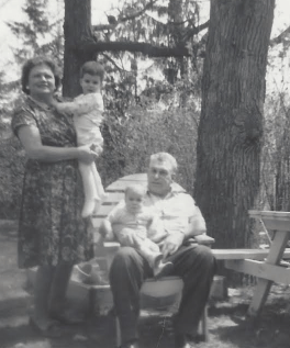 Black and white photo of our grandparents holding us. It's outside beside a big tree. Grandma is holding me - I'm about 2 years old. Kevin is on Papa's lap. He's an infant.