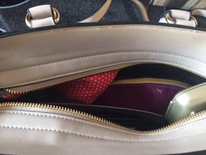 zipper opening of handbag where you can see it's already full of stuff - a small makeup bag, hearing aid container, sunglassses