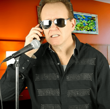 Ed Kelly standing in front of a microphone, wearing mirrored sunglasses, talking on the phone as he does one of his impressions