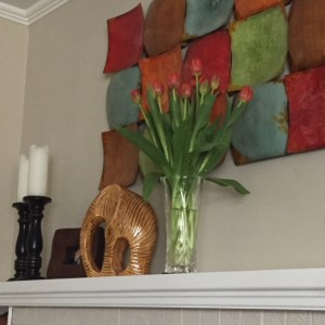 vase full of red tulips on a white fireplace mantle, beside a yellow ceramic elephant, framed picture of me and my brother and two large wooden candlesticks with white pillar candles