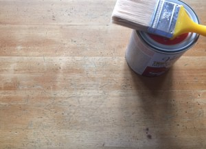 part of the pine table shows more wear. Can of top-coat and a brush sit beside it