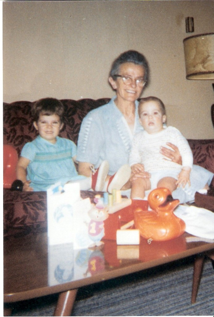 picture from the 70s of our ancient, birdlike Grandma with baby Kevin on her lap and me, a toddler, sitting beside her. All are smiling.