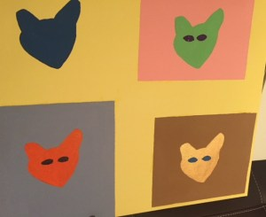Four-panel painting with a cat head in each. A wide variety of colours used for cats and backgrounds