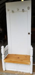 Old door painted white with five crystal doorknobs as coat hangers. A bench at the bottom features railings with newel posts on either side made from an old footboard. The bench top is varnished wood.