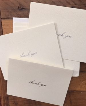 scattered cream-coloured cards with thank-you written in silver script