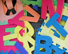 large craft letters in bright colours, strewn about in a random pile