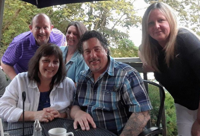 Birthday boy Jeff and his wife Laurie behind Derek and me, with our friend Carole beside Derek. We're at an outdoor table on a patio with clear sky and trees behind us.