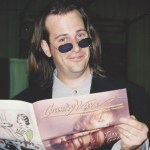 Robert Reynolds pretending to read an issue of Country Wave Magazine