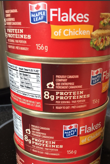 "stacked cans of Maple Leaf brand chicken breast, labelled in red, ""Flakes of Chicken"""