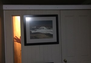 booth has a long, slim window on the left side, a print of Peggy's Cove and a closed door. White trim finishes the top and you can see Derek's hand waving in the window
