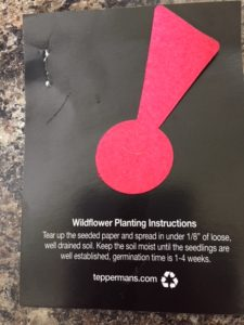 Black card with red exclamation point in felt, which is the company's logo, and an explanation underneath that the felt piece is a wildflower starter and contains seeds