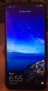 My new phone in my h and with a bright blue ocean and sky scene on the screen