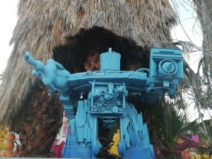 giant blue robot in front of a palm tree