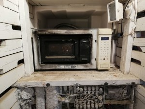 Small microwave inside a larger microwave. Both are burned and melted a bit