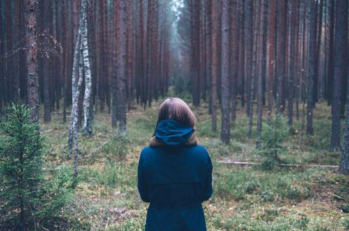 The back of a woman as she stands, seemingly wondering whether to walk into the woods