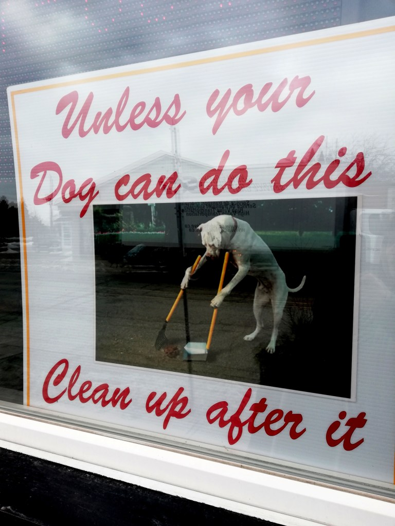 Sign shows a dog on its hind legs holding a scoop and a dustpan and it reads: Unless your dog can do this, clean up after it.