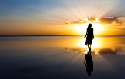 woman in silhouette walking on a beach toward the sunset