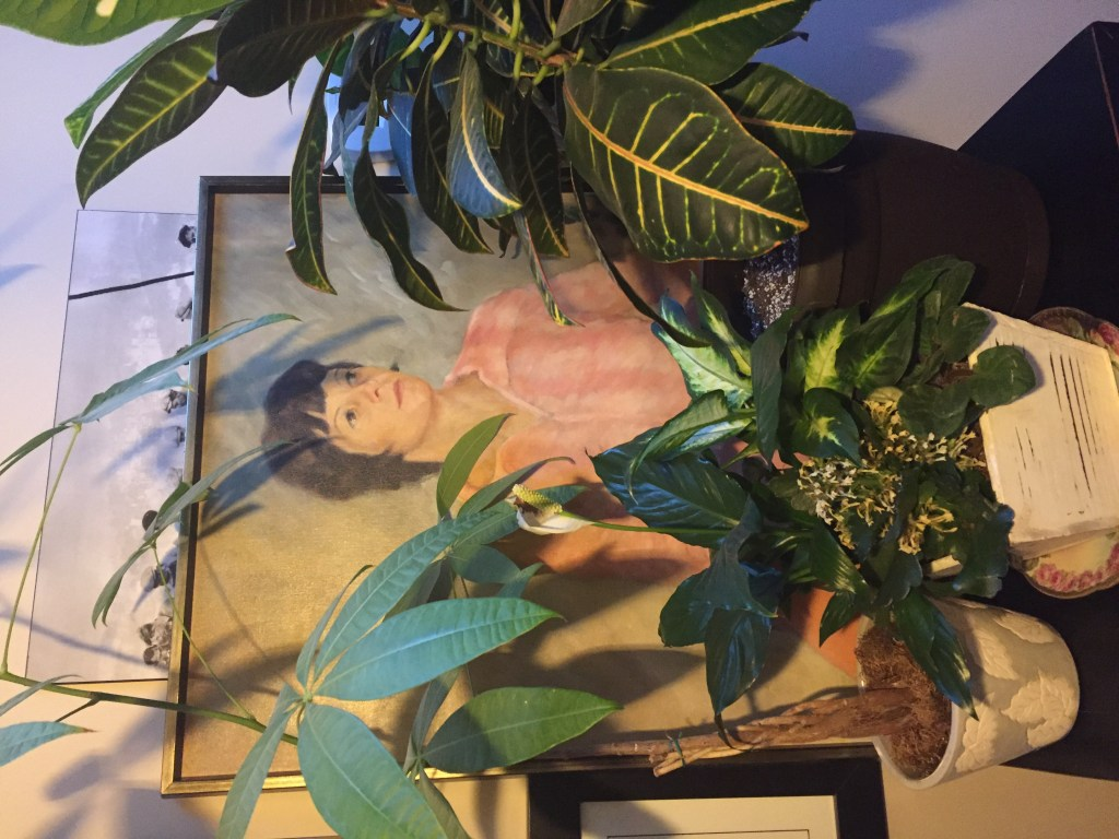 Mom's painting peeking out from behind potted plants.