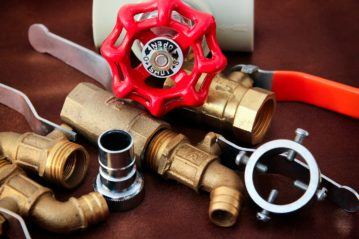 collection of plumbing materials including pipe, faucet handles and other bits and pieces