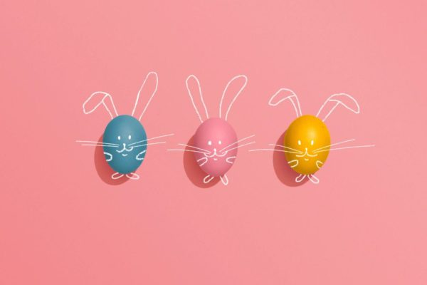three colourful easter eggs laid out on pink paper with faces and whiskers drawn on them, and bunny ears in white on the paper