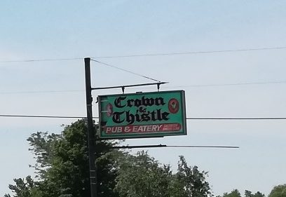Old sign, green, white and red, reads Crown and Thistle Eatery and Pub