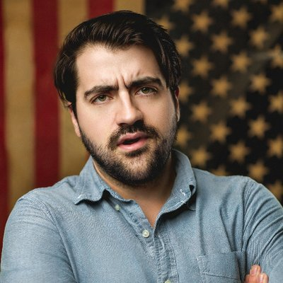 closeup of Trae Crowder from his Twitter profile - dark-haired man with a trimmed moustache and beard wearing a light denim shirt